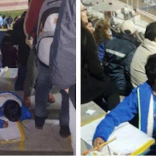 Aplicado niño lleva su tarea hasta un partido de futbol